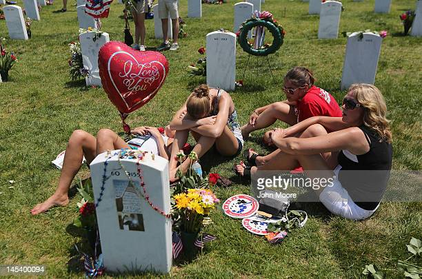 Randi Meinert grieves with family members over her slain brother's grave at the National Cemetery on Memorial Day on May 28 2012 in Arlington...