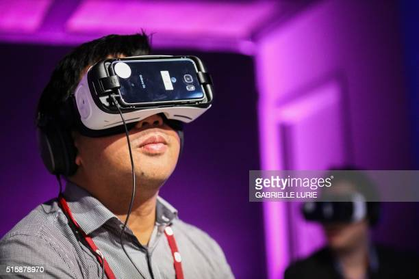 Randolph Ramsay of GameSpot wears Oculus goggles as he tries out Minecraft for Gear VR during a press demonstration at The Village event space in San...