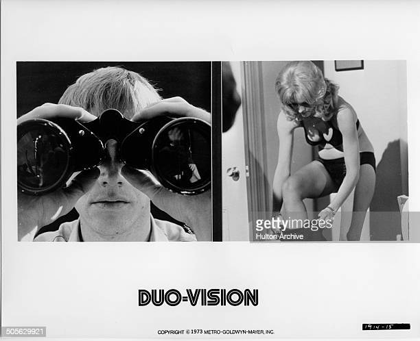 Randolph Roberts peers through binoculars Diane McBain dresses in a scene from the MGM movie Wicked Wicked circa 1973