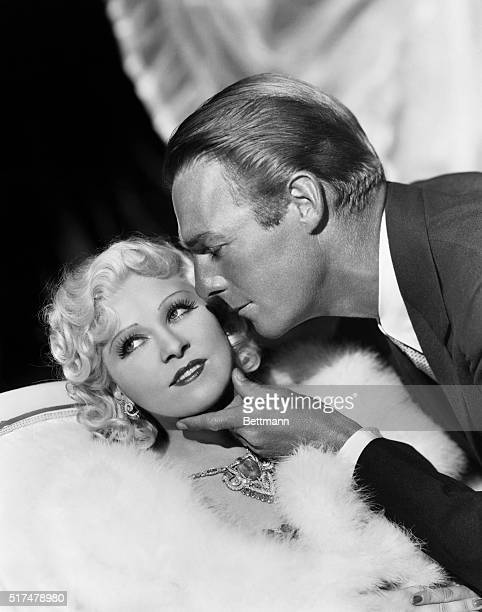 Randolph Scott caresses Mae West's chin in this publicity still from the 1936 motion picture, Go West Young Man.