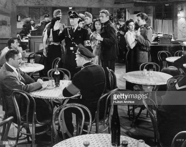 Randolph Scott eludes the Gestapo by dancing with a regular of La Coquin Cafe, in a scene from the Universal picture 'Paris Calling'.