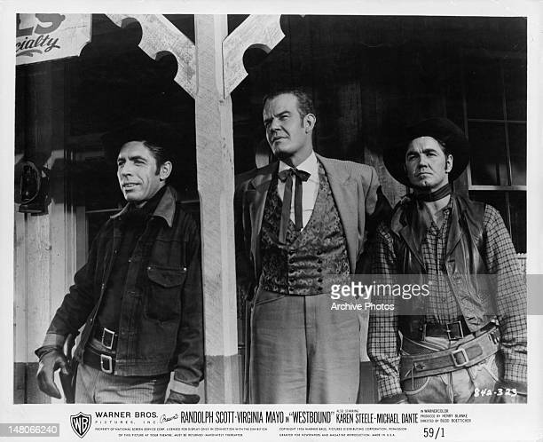 Randolph Scott standing with two other men in front of a saloon in a scene from the film 'Westbound' 1958