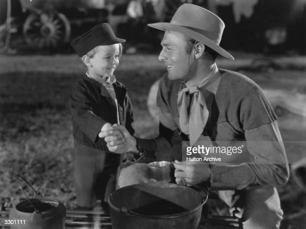 Randolph Scott the outdoor star is making friends with Billy Lee the child star in a scene from the film 'Wagon Wheels'