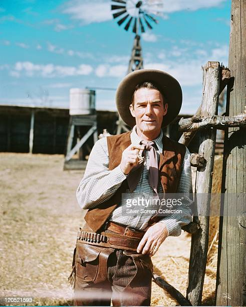 Randolph Scott US actor in a western costume with cowboy hat a suede waistcoat and tan leather chaps holding a piece of straw in his mouth in a...