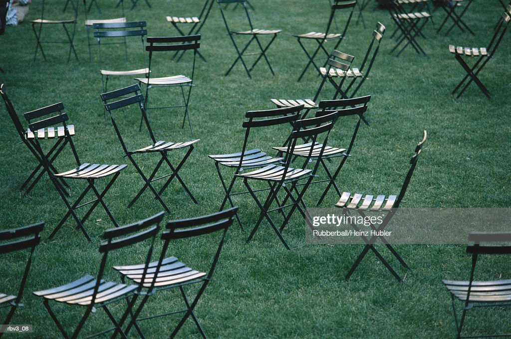 random chairs rest on green grass on a lawn : Foto de stock