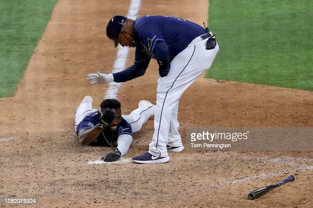 Randy Arozarena of the Tampa Bay Rays is helped up by first base coach Ozzie Timmons after scoring the game winning run to defeat the Los Angeles...