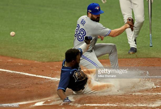 Randy Arozarena of the Tampa Bay Rays scores a run on a passed ball as Robbie Ray of the Toronto Blue Jays fields the throw in the fourth inning...
