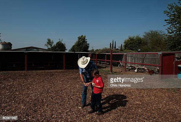 Randy Bekendam takes eggs from his grandson Christian Owen after they harvested them on their property known as Amy's Farm April 7, 2008 in Ontario,...