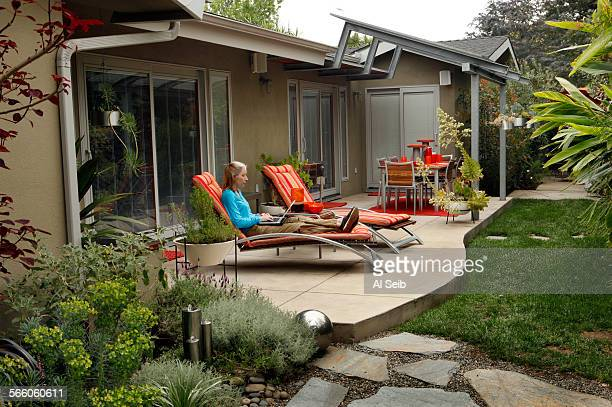 Randy Bergman works on her computer through her wireless connection as she relaxes in the backyard of her home in the Cheviot Hills neighborhood of...