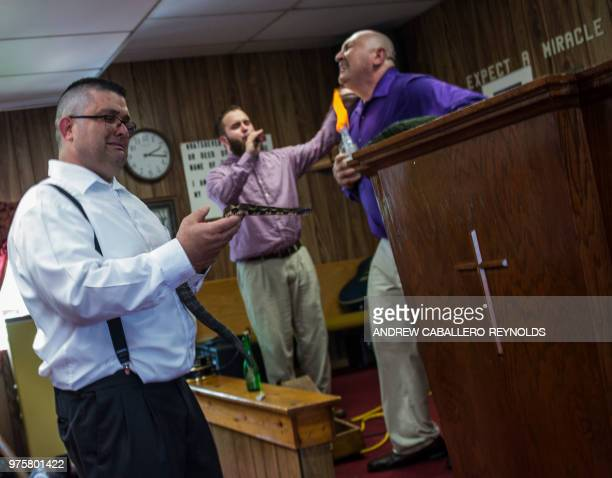 Randy Brandon holds a timber rattle snake as Pastor Chris Wolford puts a flame to his chin during a Pentecostal serpent handlers service at the House...