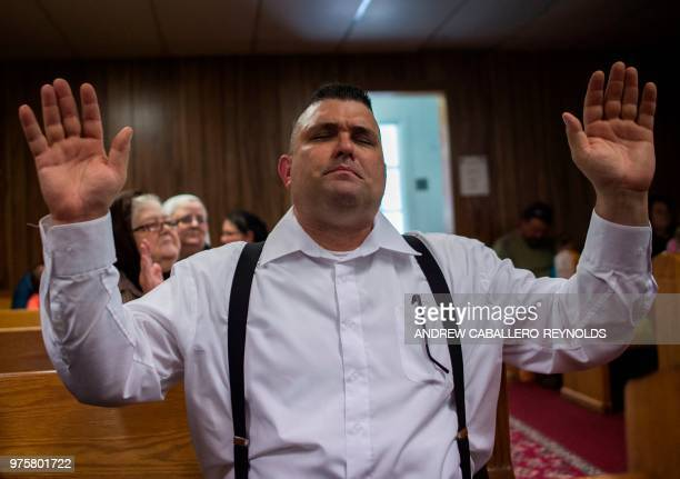 Randy Brandon raises his hands as he prays during a Pentecostal serpent handlers service at the House of the Lord Jesus church in Squire West...