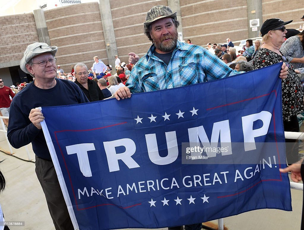 Randy Bridges (L) of Nevada and Ben Jordan of Utah, both supporters of Republican presidential nominee Donald Trump, carry a Trump flag during a campaign rally at the Henderson Pavilion on October 5, 2016 in Henderson, Nevada. Trump is campaigning ahead of the second presidential debate coming up on October 9 with Democratic presidential nominee Hillary Clinton.