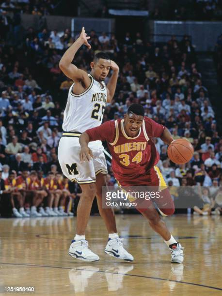 Randy Carter, Center for the University of Minnesota Golden Gophers dribbles the ball past Juwan Howard of the University of Michigan Wolverines...