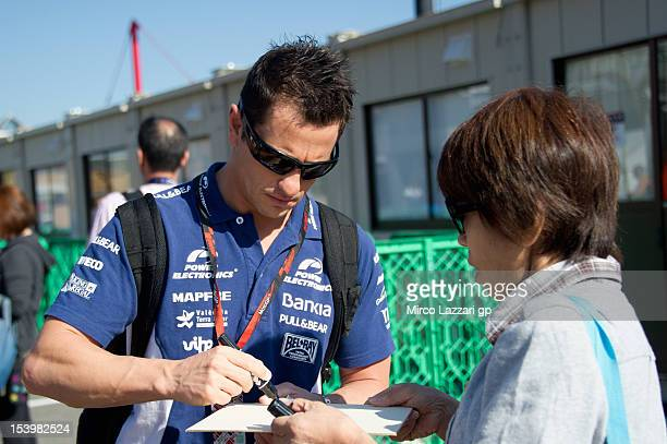 Randy De Puniet of France and Power Electronics Aspar signs autographs for fans during the pit walk during the free practice of the MotoGP Of Japan...