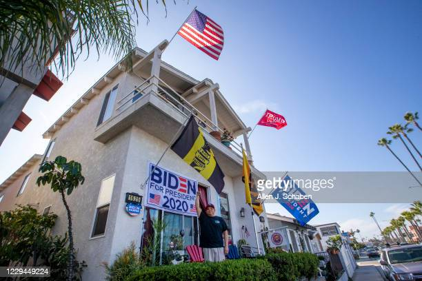 Randy Duarte, who supports Presidential candidate Joe Biden, stands amidst his supportive flags while the upstairs tennant is a President Donald...