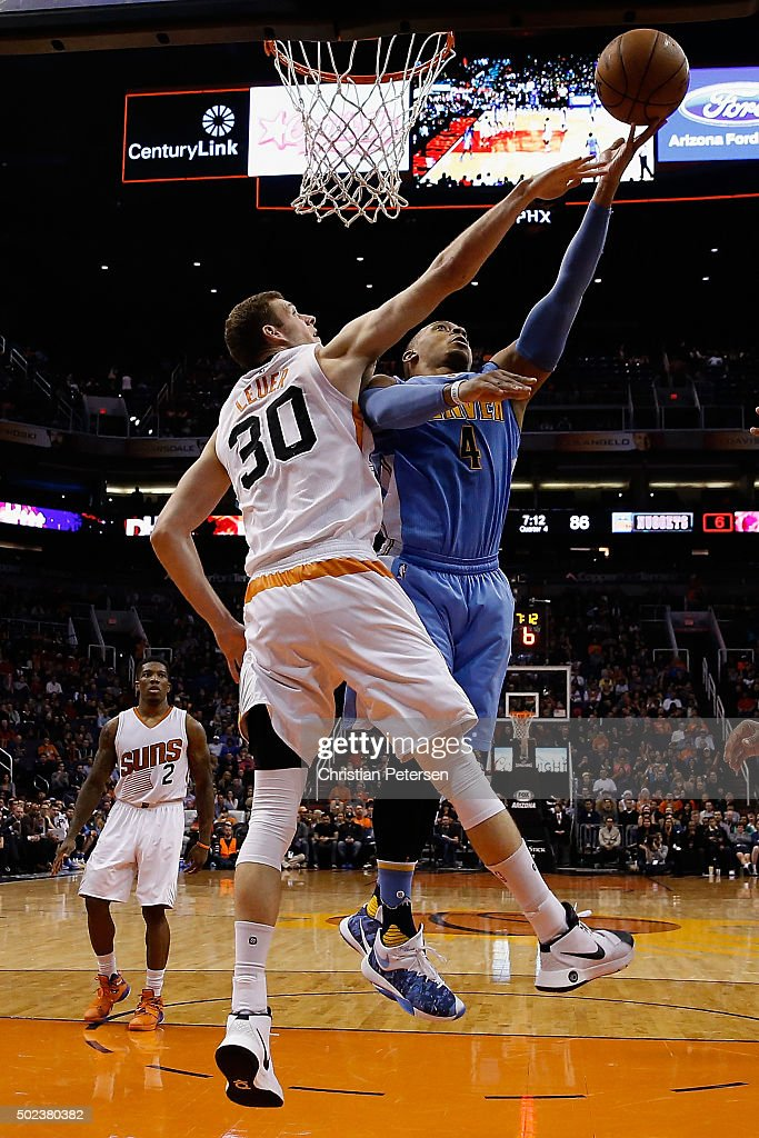 Randy Foye #4 of the Denver Nuggets lays up a shot past Jon Leuer #30 of the Phoenix Suns during the second half of the NBA game at Talking Stick Resort Arena on December 23, 2015 in Phoenix, Arizona. The Nuggets defeated the Suns 104-96.