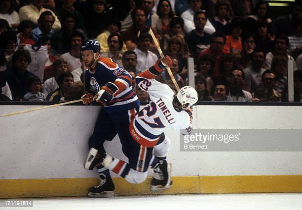 Randy Gregg of the Edmonton Oilers is checked by John Tonelli of the New York Islanders during the 1984 Stanley Cup Finals in May 1984 at the Nassau...