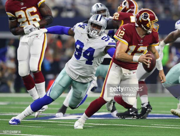 Randy Gregory of the Dallas Cowboys tries to grab Colt McCoy of the Washington Redskins in a football game at ATT Stadium on November 22 2018 in...