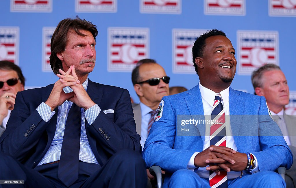 Randy Johnson and Pedro Martinez sit as the Hall of Fame Induction Ceremony begins at National Baseball Hall of Fame on July 26, 2015 in Cooperstown, New York. Johnson was inducted with Pedro Martinez,Craig Biggio and John Smoltz