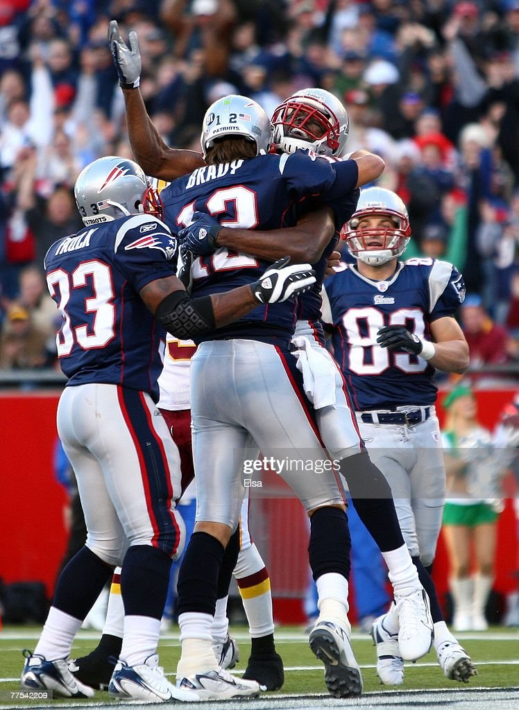 Randy Moss #81, Kevin Faulk #33 and Wes Walker #83 of the New England Patriots congratulate Tom Brady #12 after Brady ran the ball in for a touchdown in the first quarter against the Washington Redskins at Gillette Stadium October 28, 2007 in Foxboro, Massachusetts.