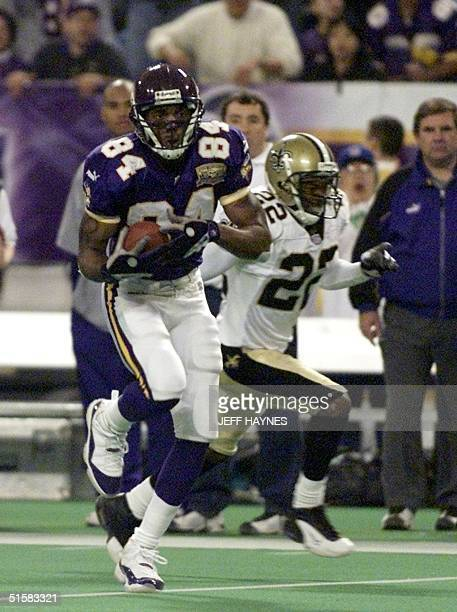 Randy Moss of the Minnesota Vikings runs past Fred Thomas of the New Orleans Saints on his way to the first touchdown of the game 06 January 2001...