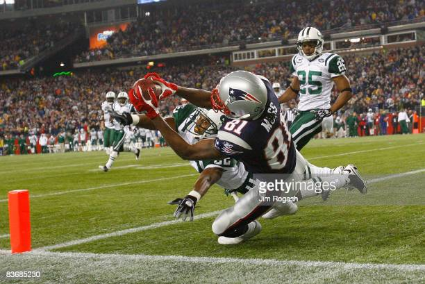 Randy Moss of the New England Patriots catches a touchdown pass against the defense of Ty Law and Kerry Rhodes of the New York Jets sending the game...
