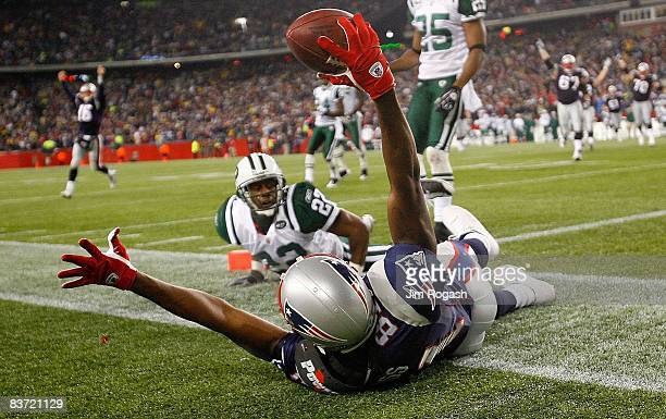 Randy Moss of the New England Patriots catches a touchdown pass against the defense of Ty Law and Kerry Rhodes of the New York Jets at Gillette...