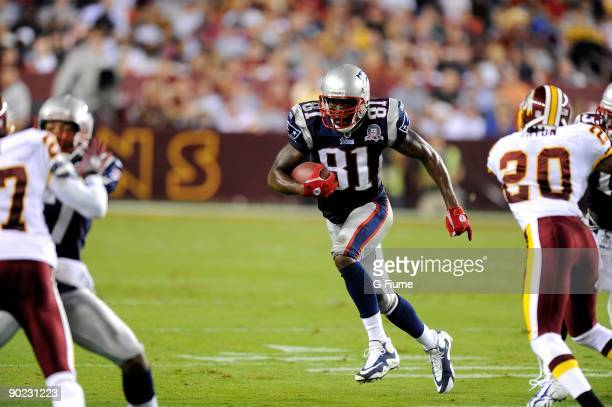 Randy Moss of the New England Patriots runs with the ball after catching a pass during a preseason game against the Washington Redskins at FedEx...