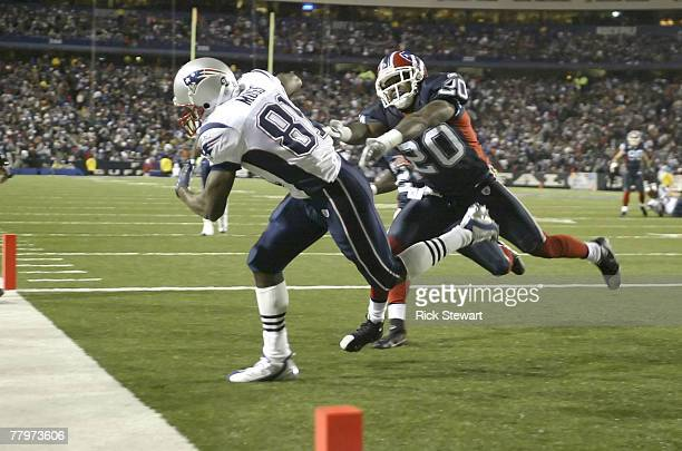 Randy Moss of the New England Patriots scores his fourth touchdown of the first half ahead of Donte Whitner of the Buffalo Bills at Ralph Wilson...