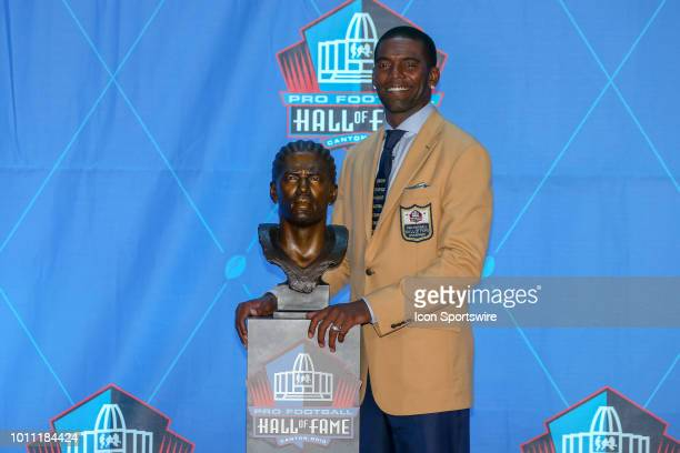 Randy Moss poses for photographers next to his Hall of Fame bust after he was enshrined into the Pro Football Hall of Fame during the 2018 Pro...