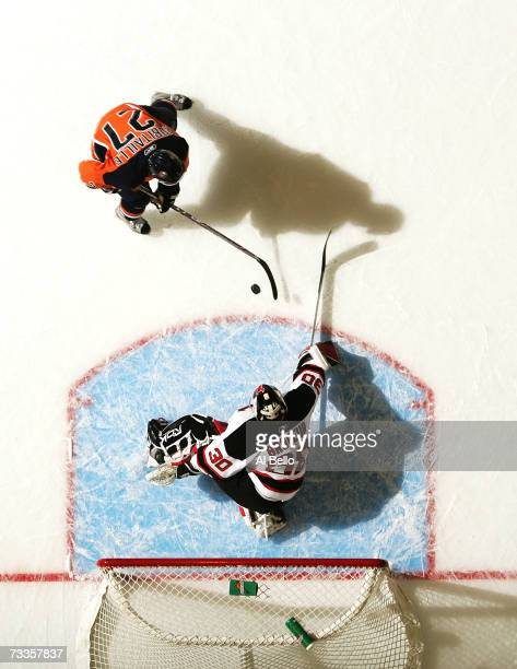 Randy Robitaille of the New York Islanders shoots the puck against Martin Brodeur of the New Jersey Devils during their game at the Nassau Coliseum...