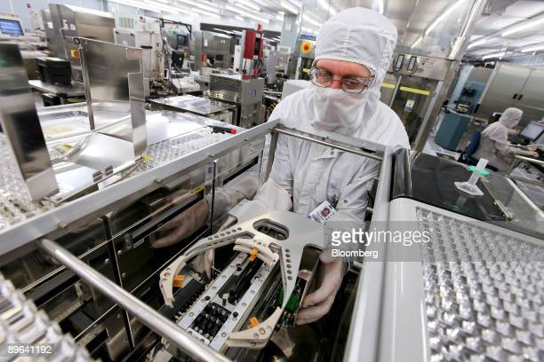Randy Siems prepares to load a silicon wafer machine in a clean room at the Texas Instruments semiconductor fabrication plant in Dallas Texas US on...