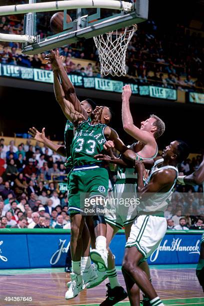 Randy White of the Dallas Mavericks rebounds the ball against Larry Bird of the Boston Celtics during a game played in 1992 at the Boston Garden in...