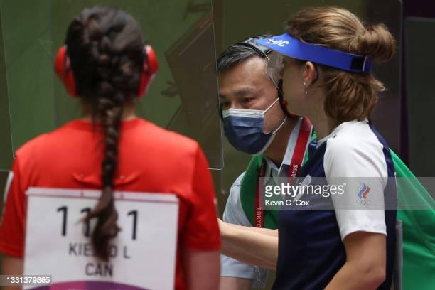Range officer fixes the plexiglass next to Vitalina Batsarashkina of Team ROC in 25m Pistol Women's Qualification on day seven of the Tokyo 2020...