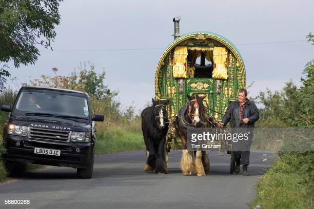 Range Rover car overtakes shire horsedrawn gypsy caravan on country lane StowOnTheWold Gloucestershire United Kingdom