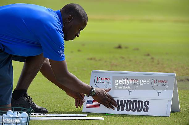 A range volunteer applies Tiger Woods name on a sign on the driving range before the first round of the Hero World Challenge at Albany course on...