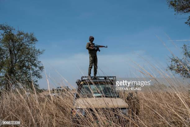 TOPSHOT A ranger stands guard on top of a vehicle during an elephant collaring exercise at Pendjari National Park near Tanguieta on January 10 2018 A...