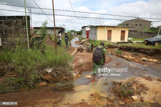 A ranger walks though a stream of water in the Angondje district of Libreville on May 17 2018 where houses have been mushrooming without any coherent...