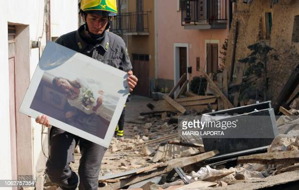 Rangers carries on April 9, 2009 a portrait of a woman who was killed along with her mother and father during the April 6 earthquake in the village...