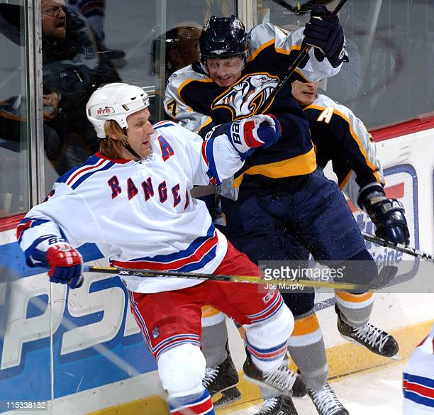 Rangers Darius Kasparaitis is checked by Scott Hartnell of the Predators during the game between the New York Rangers and the Nashville Predators at...