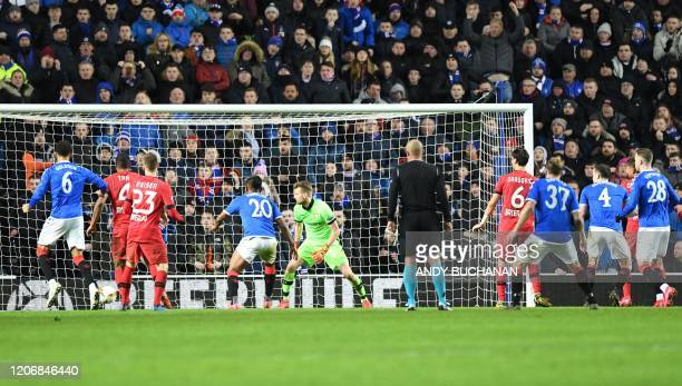 Rangers' English defender George Edmundson scores his team's first goal during the UEFA Europa League round of 16 first leg football match between...