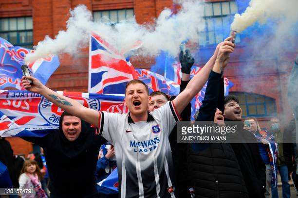 Rangers fans celebrate with flags and smoke grenades outside Ibrox Stadium, home of Rangers Football Club, in Glasgow on March 7, 2021 after their...