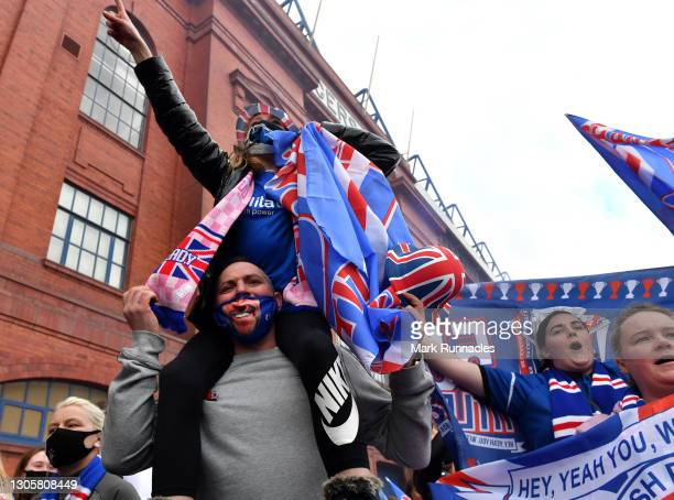 Rangers fans, gather with flags outside the Ibrox Stadium, to celebrate their team winning the Scottish Premiership title on March 07, 2021 in...