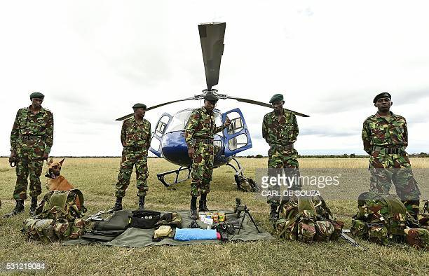 Rangers from Ol Pejeta Sanctuary's stand next to their unpacked bags in front of a helicopter as the tactical anti poaching response team carry out a...
