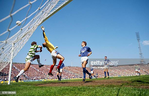 Rangers goalkeeper Chris Woods tips the ball over the crossbar under pressure from a Celtic player as defender Richard Gough looks on during the 1989...