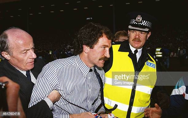 Rangers manager Graeme Souness is escorted off the field after Rangers had clinched the League title for the 1989/90 season by beating Dundee United...