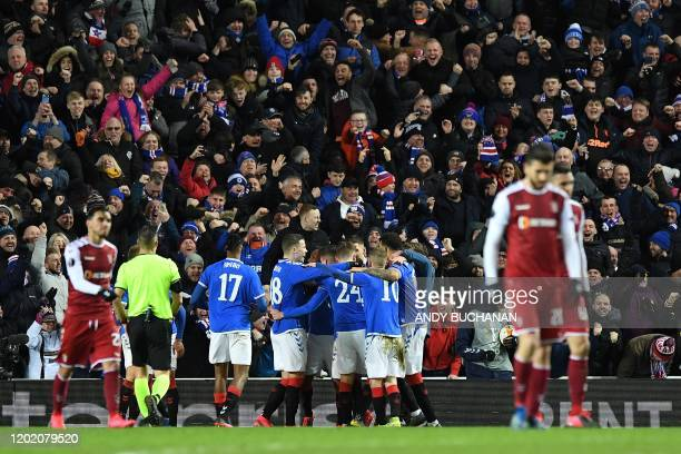 Rangers' Romanian midfielder Ianis Hagi is mobbed by teammates after scoring his team's third goal during the UEFA Europa League round of 32 first...