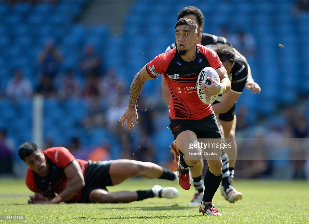 Rangi Chase of Salford Red Devils breaks through the tackles of Jon Clarke and Magraff Leuluai of Widnes Vikings to score his first half try during the Super League match between Widnes Vikings and Salford Red Devils at Etihad Stadium on May 17, 2014 in Manchester, England.