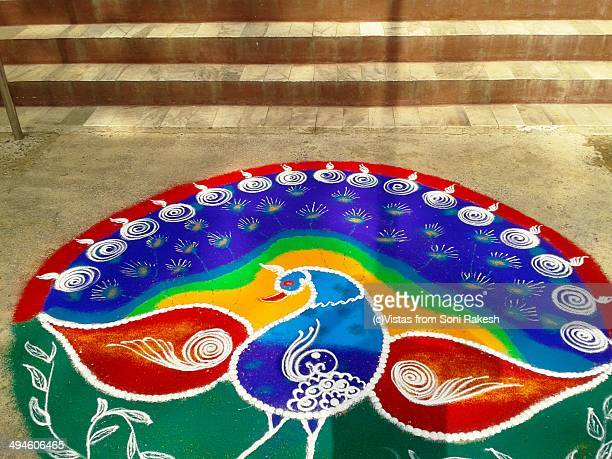 Rangoli depicting a colourful peacock at a doorste