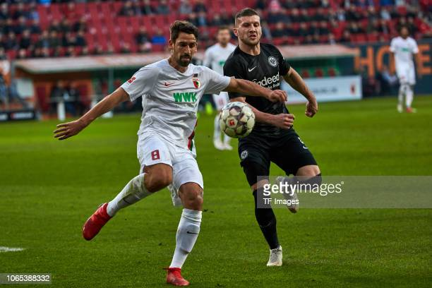 Rani Khedira of Augsburg and Ante Rebic of Frankfurt battle for the ball during the Bundesliga match between FC Augsburg and Eintracht Frankfurt at...